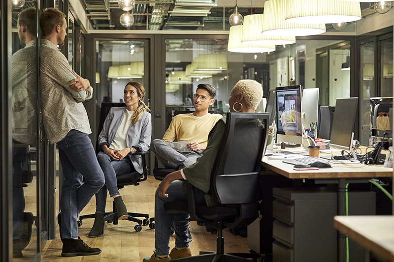 Business professionals listening to coworker in creative office. Male and female colleagues are discussing at workplace. They are wearing smart casuals.